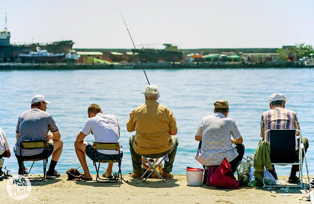 Пять рыбаков на набережной